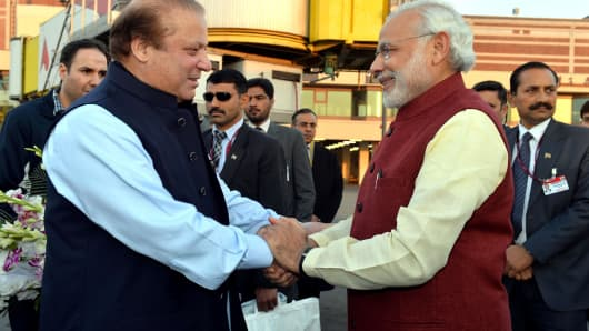 Prime Minister of Pakistan Nawaz Sharif (L) shakes hands with Indian Prime Minister Narendra Modi (R) at Allama Iqbal International Airport in Lahore, Pakistan on December 25, 2015.