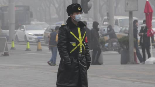 A Chinese man walking on a street wears a mask amid heavy smog in Beijing, China on December 25, 2015. Hazardous smog blanketing China's north-east has sparked more red alerts, with authorities advising residents in 10 cities to stay indoors.