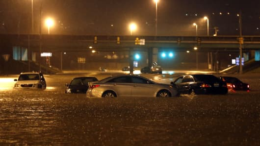 Cars sit submerged in flood waters on Tallapoosa Street, Friday, Dec. 25, 2015, in Birmingham, Ala. A Christmastime wave of severe weather continued Friday as a tornado touched down in north-central Alabama, including part of Birmingham, the state's largest city.