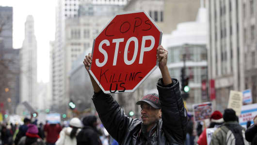 A protester at a march on Michigan Avenue, Chicago, on December 24, holds up a sign referring to Laquan McDonald, 17. Police officer Jason Van Dyke was charged last month with McDonald's murder.