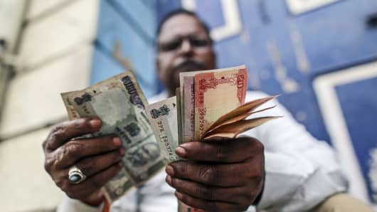 A man counts Indian rupee banknotes for a photograph near the Bombay Stock Exchange (BSE) building in Mumbai, India.