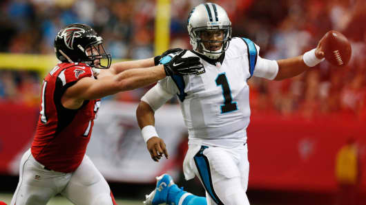 Carolina Panthers quarterback Cam Newton (1) is chased by Atlanta Falcons linebacker Kroy Biermann (71) at the Georgia Dome, Dec. 27, 2015.