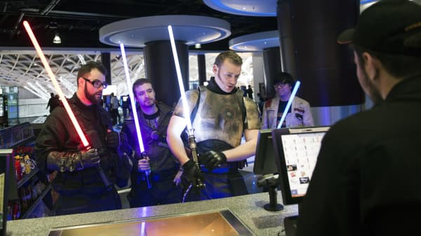 "Customers holding lightsabers and dressed as Jedi Knights collect their tickets from the counter at the first public screening of Walt Disney's ""Star Wars: The Force Awakens"" at a Vue Entertainment cinema in London."