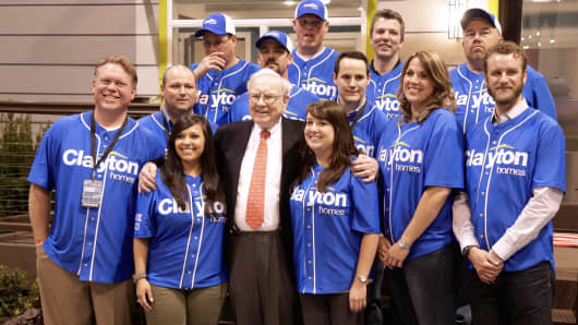 Warren Buffett poses with employees of Clayton Homes while touring the exhibition floor of Berkshire Hathaway's annual shareholders meeting in Omaha, Neb., May 2, 2014.