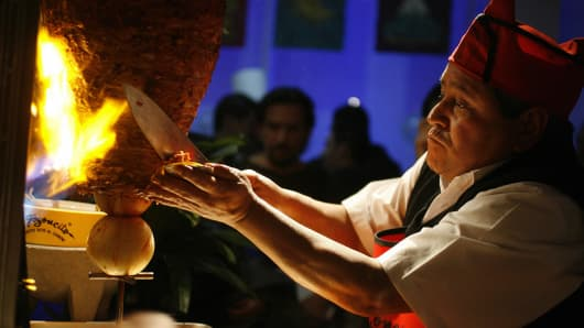 Mexican chef Alberto Juarez Don Beto slices grilled meat onto a hand-held tortilla for a taco al pastor