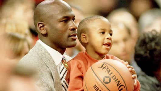Retired Chicago Bulls basketball star Michael Jordan holds his son Marcus, November 6, 1993, as they watch a Bulls game in Chicago.