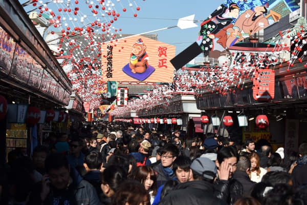 Visitors walk underneath New Year's Day decorations celebrating next year's 'Year of the Monkey' from the Chinese zodiac, at the Nakamise shopping alley in front of Sensoji Temple in Tokyo on December 26, 2015.