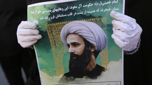 An Iranian woman holds a portrait of prominent Shiite Muslim cleric Nimr al-Nimr during a demonstration against his execution by Saudi authorities, on January 3, 2016.