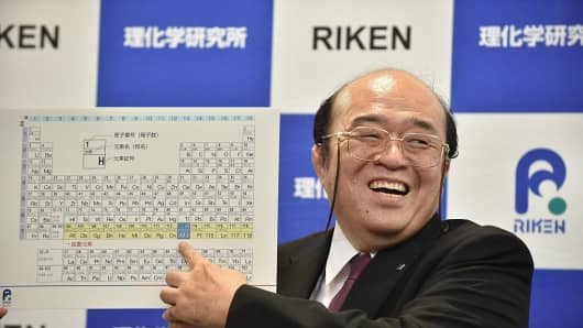 Kosuke Morita, the leader of the Riken team, smiles as he points to a board displaying the new atomic element 113 during a press conference in Wako, Saitama prefecture on December 31, 2015.
