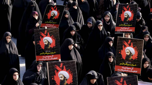 Iranian protesters in Tehran hold pictures of Shiite cleric Nimr al-Nimr during a Jan. 4, 2016, demonstration against his execution by Saudi Arabia.