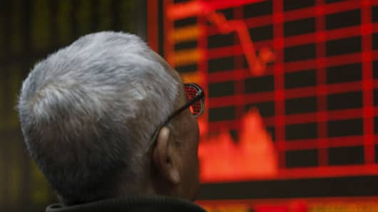 A man looks at an electronic board showing stock information at a brokerage house in Beijing, China, on Jan. 4, 2016.