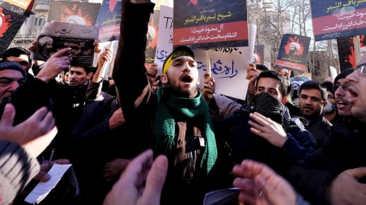 Iranian protesters chant slogans as they hold pictures of Shi'ite cleric Sheikh Nimr al-Nimr during a demonstration against the execution of Nimr in Saudi Arabia, outside the Saudi Arabian Embassy in Tehran January, 3, 2016.