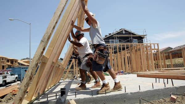 Construction workers raise wood framing as they build homes in a new housing development in Richmond, Calif.