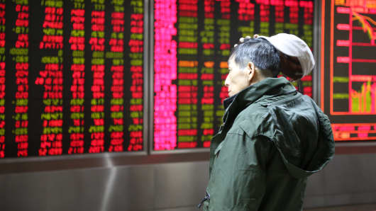 An investor observes stock market at a stock exchange hall on December 14, 2015 in Beijing, China.