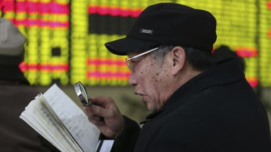 An investor uses a magnifying glass to read a notebook in front of an electronic board showing stock information at a brokerage house in Nantong, Jiangsu province, China, January 5, 2016.
