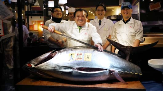 Kiyomura K.K. President Kiyoshi Kimura, poses with a fresh bluefin tuna after the year's first auction at Tsukiji Market on January 5, 2016 in Tokyo.