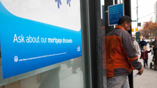 A man exits a Citibank branch with window advertising for mortgages, in New York.