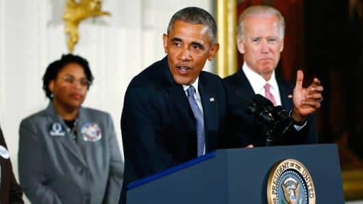 President Barack Obama stands with Vice President Joe Biden (R) and family members of shooting victims while speaking about gun violence in the East Room of the White House in Washington January 5, 2016.