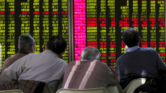 Men look an electronic board showing stock information at a brokerage house in Beijing, China, January 5, 2016.