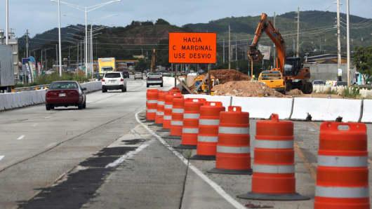 Cars pass a construction site in Fajardo, near San Juan, Puerto Rico, on Dec. 1, 2015.