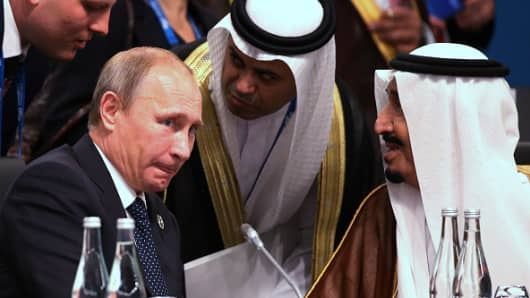 Salman bin Abdulaziz, deputy prime minister and crown prince of Saudi Arabia, right, speaks with Vladimir Putin, Russia's president, seated left, during a plenary session at the Group of 20 (G-20) summit in Brisbane, Australia.