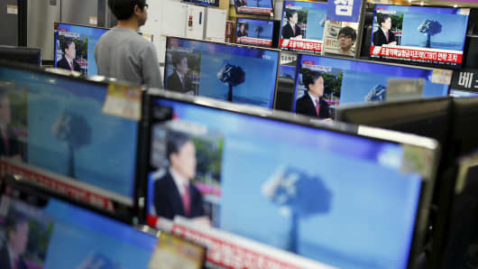 A sales assistant watches TV sets broadcasting a news report on North Korea's nuclear test, in Seoul, January 6, 2016.