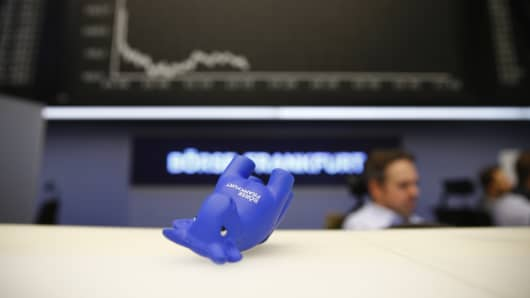 A styrofoam bull figure lies on its side on a counter in front of the German share price index DAX board at Frankfurt's stock exchange in Frankfurt, Germany January 7, 2016.