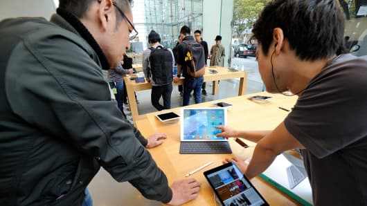 An apple shop assistant demonstrates an Ipad pro at the Apple store of the High-end shopping district of Omotesando in Tokyo, Japan.
