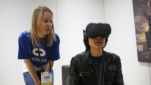 Alison Weber, left, instructs Peijun Guo on using the Oculus Rift VR headset at the Oculus booth at CES International, Wednesday, Jan. 6, 2016, in Las Vegas.