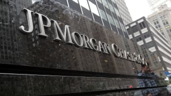 A man is reflected in a sign outside of the JPMorgan Chase headquarters in New York City.