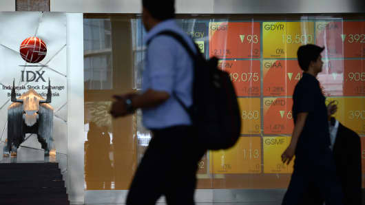 People walk past an electronic board displaying share prices at the Indonesia Stock Exchange (IDX) in Jakarta.