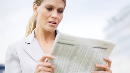investor reading financial newspaper