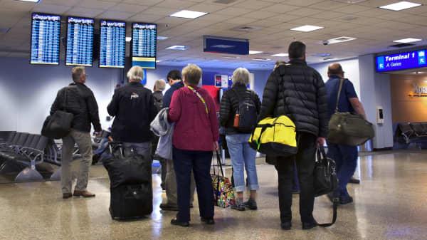 Airplane passengers check their flights on departure boards at Salt Lake City International Airport in Salt Lake City, Utah.