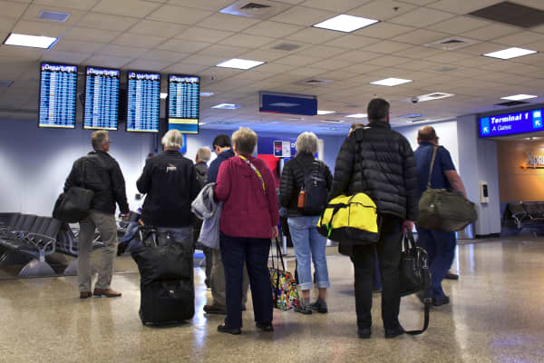 Airplane passengers check their flights on departure boards at Salt Lake City International Airport in Salt Lake City, Utah.