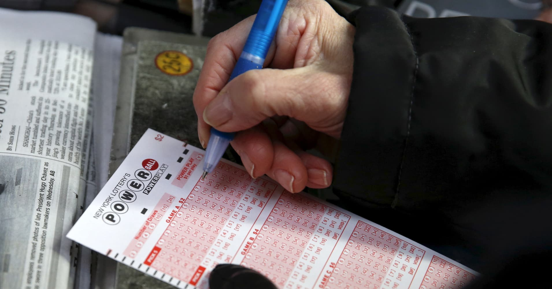 A woman fills out a ticket for the $700 million Powerball lottery draw at Times Square in the Manhattan borough of New York.