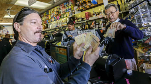 Mark Nelson, left, shows off $460 worth of Powerball lottery tickets he bought at Bluebird Liquor, a shop with a reputation for lottery luck, in Hawthorne. On right is owner of liquor store James Kim.