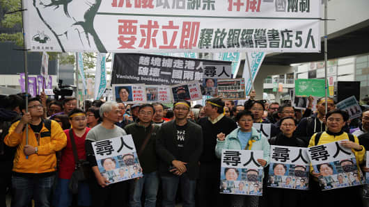 People hold placards showing some of the missing booksellers from Hong Kong's Mighty Current publishing house known for books critical of Beijing, during a protest in Hong Kong on January 10, 2016.