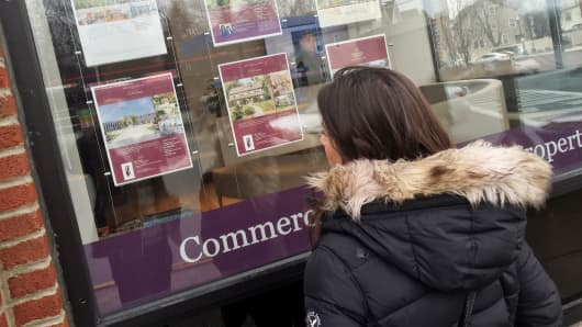A woman looks at real estate postings outside a Berkshire Hathaway Home Services office in Montclair, N.J.
