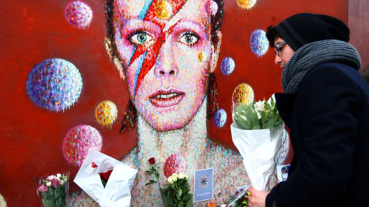 A man leaves flowers at a mural of David Bowie in Brixton on Jan. 11, 2016 in London.