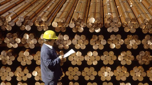 An employee takes inventory of bars of copper.