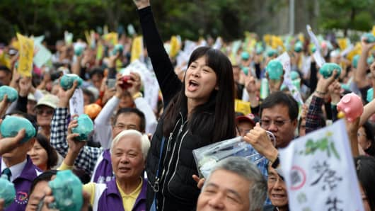 Supporters at Taiwan's main opposition Democratic Progressive Party (DPP) hold up piggy banks at a party fundraiser in Taipei.