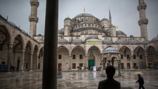 Tourists hold umbrellas to shelter from the rain in the central square inside the Blue Mosque, also known as the Sultan Ahmed, in Istanbul, Turkey, on Friday, June 14, 2013