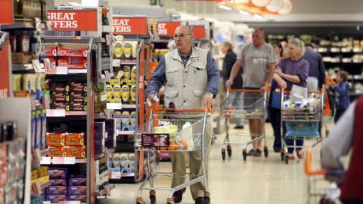 Customers push shopping carts as they look for goods inside a Sainsbury's supermarket store.