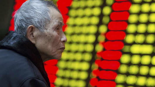 An investor looks at an electronic board showing stock prices at a brokerage house in Nanjing, China.