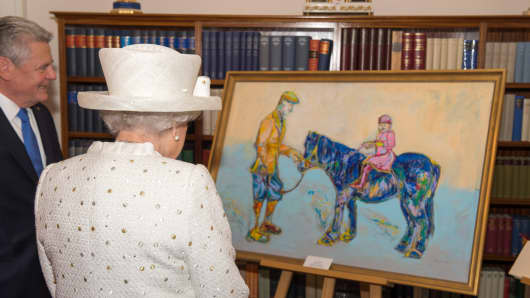 President of Germany Joachim Gauck presents Queen Elizabeth II with a painting of her and father when she was a little girl at the Schloss Bellevue Palace.
