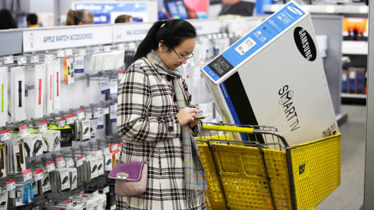 A customer uses her mobile phone as she shops at a Best Buy in Skokie, Ill.