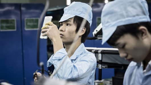 An employee inspects an OnePlus X smartphone at the OnePlus manufacturing facility in Dongguan, China.