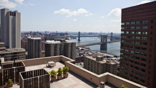 A view of Manhattan Bridge, rear, and Brooklyn Bridge, as seen from the roof terrace of a luxury condo building in New York.