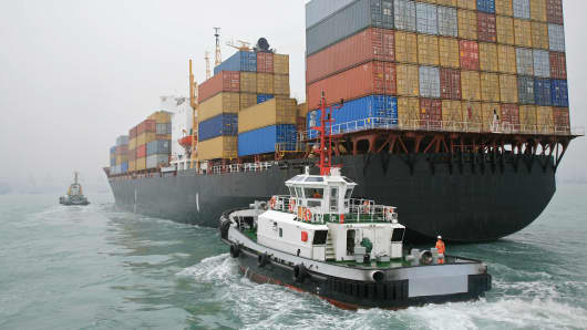 A tugboat sails alongside a container ship in Hong Kong Harbor, China.