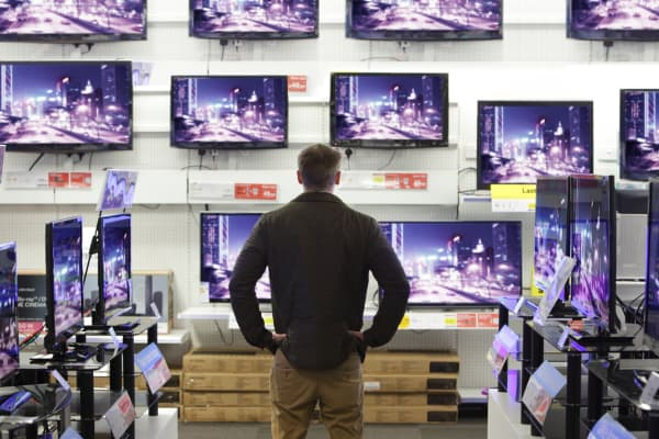 Man looking at Tvs